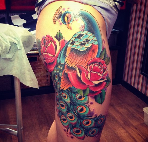 Old school style colored thigh tattoo of large peacock with flowers