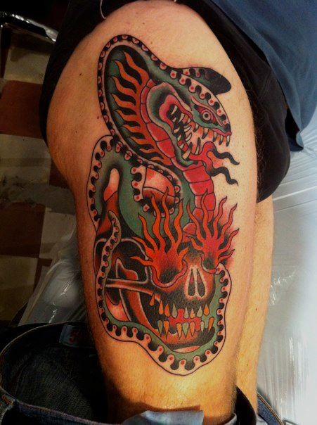 Old school style colored thigh tattoo of big snake with human skull with burning eyes