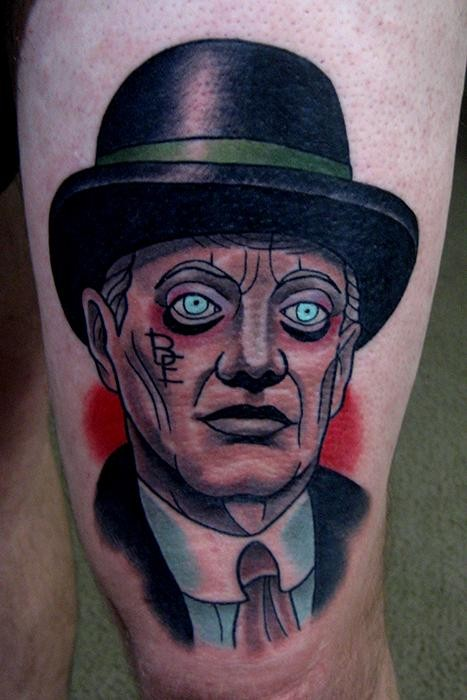 Old school style colored thigh tattoo of man face with heat