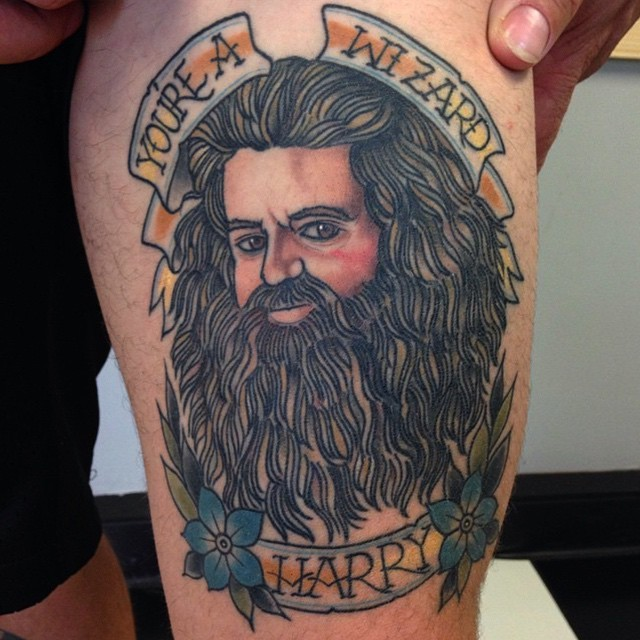 Old school style colored thigh tattoo of Harry Potter movie wizard with lettering