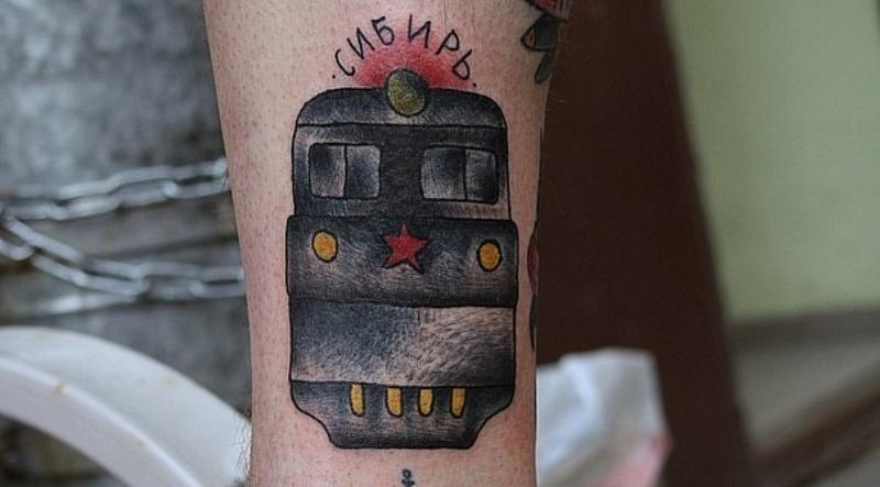 Vista frontale del treno colorato in stile vecchia scuola con stella rossa e tatuaggio con iscrizione russa