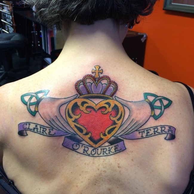 Old school style colored upper back tattoo of hands holding heart with cross and lettering