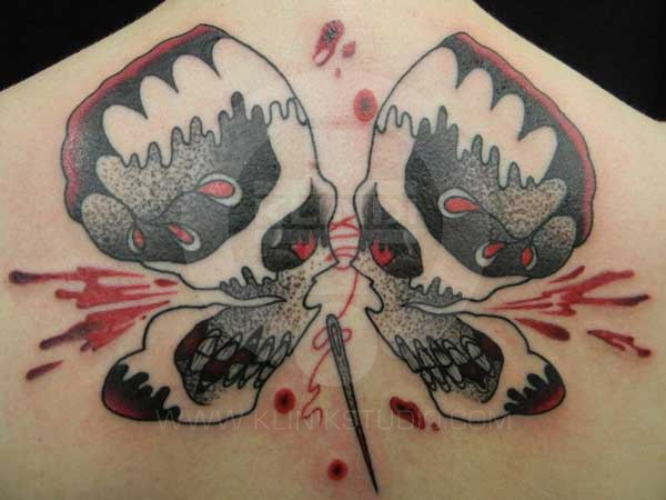 Old school style colored upper back tattoo of butterfly shaped human skulls