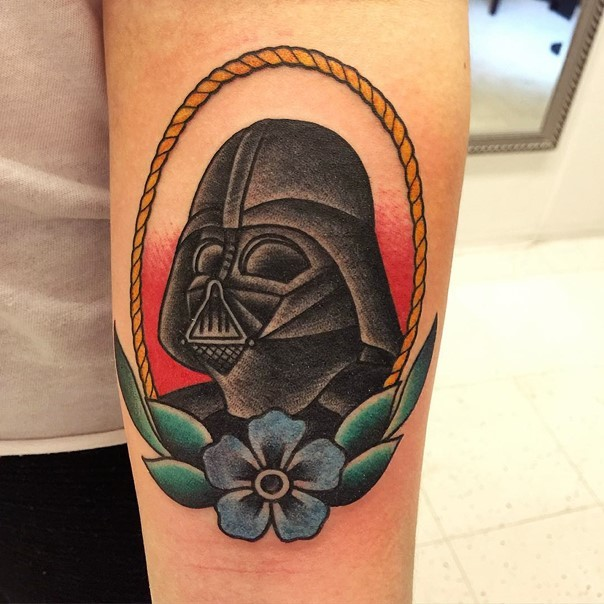 Old school style colored Vaders portrait tattoo on forearm stylized with flower