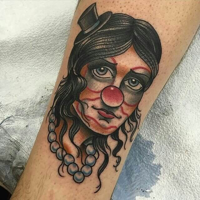 Old school style colored woman clown portrait tattoo on leg