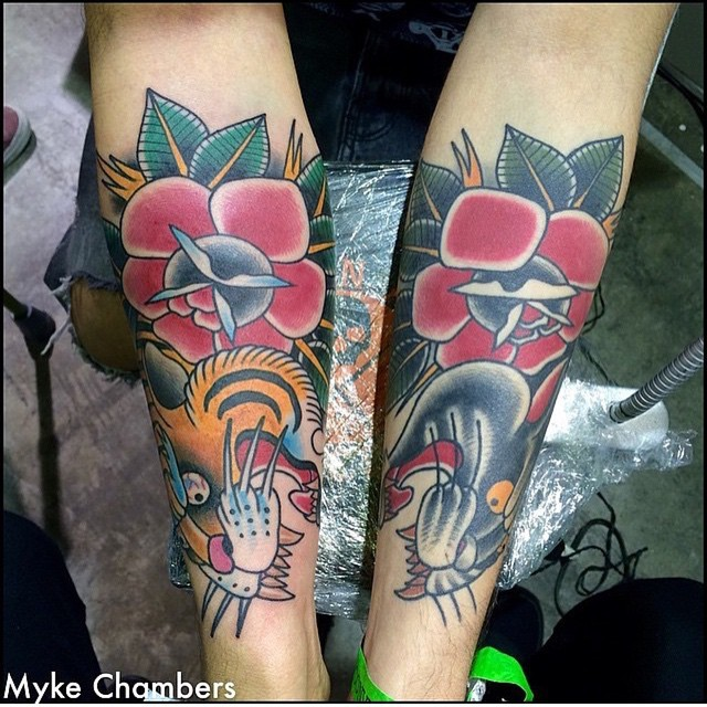 Old school style colorful tiger and black panther tattoo on forearms stylized with flowers