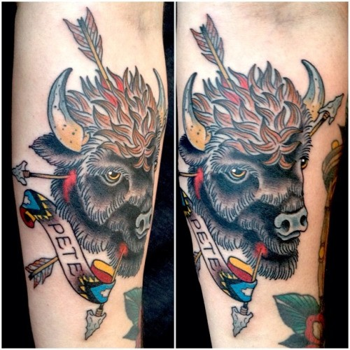 Old school style designed bulls head forearm tattoo stylized with arrows and lettering