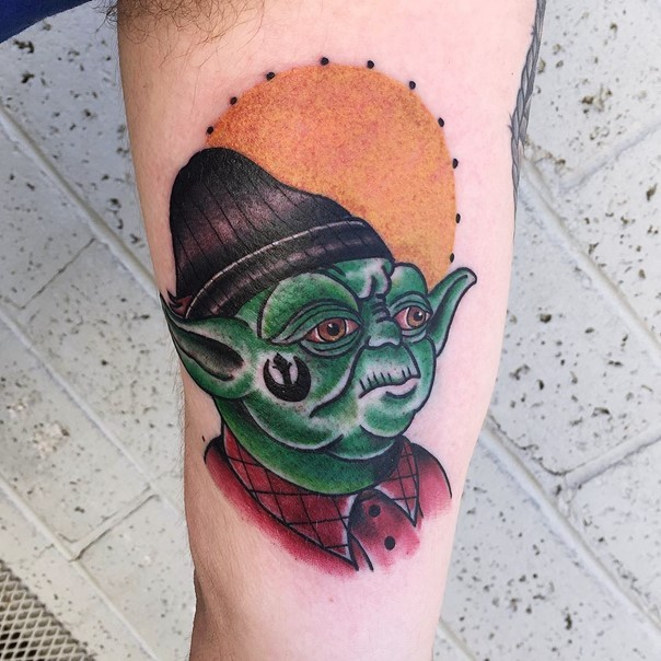 Old school style designed colored Yoda in funny hat tattoo on arm