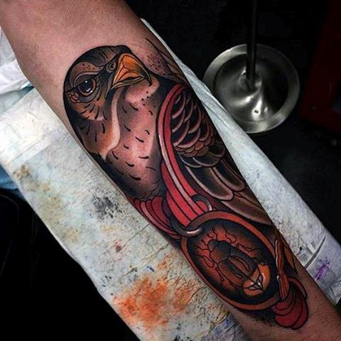 Old school style painted and colored eagle with medal tattoo on arm