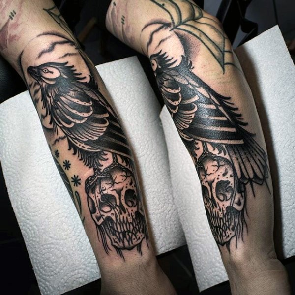 Old school style painted black and white bird with skull tattoo on arm