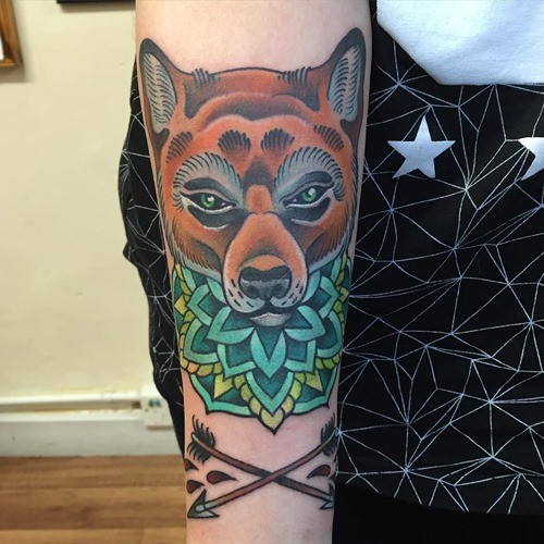 Old school style painted demonic fox tattoo on forearm combined with crossed arrows