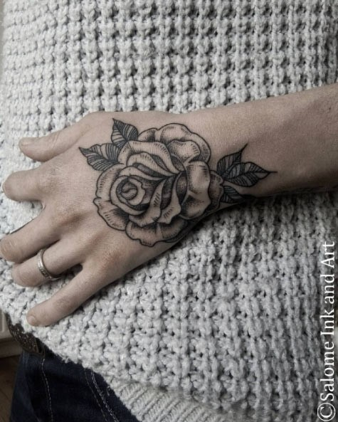 Old school style rose flower tattoo on hand with tiny details