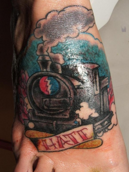 Old school style small feet tattoo of train and lettering