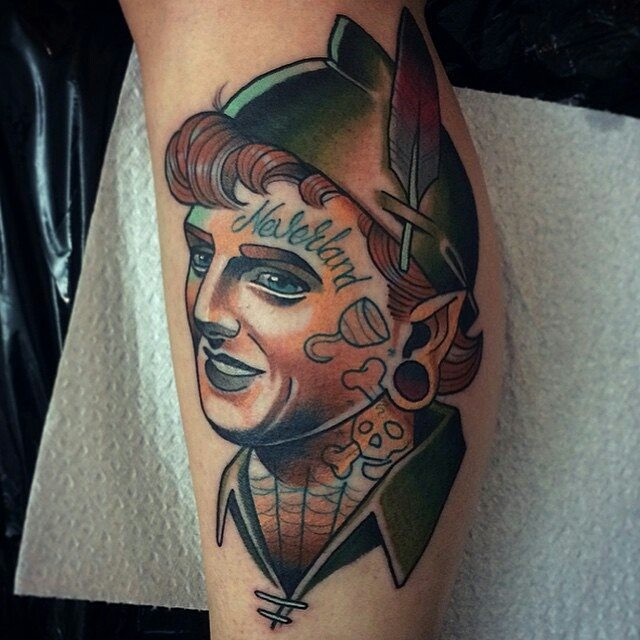 Old shool style colored leg tattoo of Peter Pan portrait with lettering