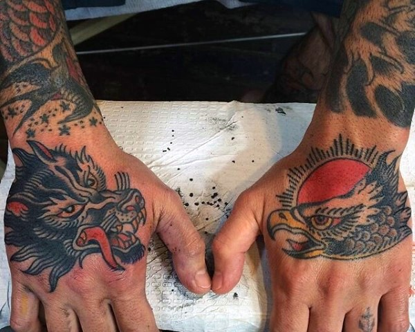 Old style designed colored eagle and wolf head tattoo on hands