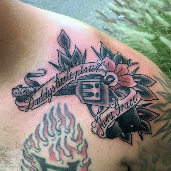 Old style gun with flower colored tattoo on shoulder with banner lettering