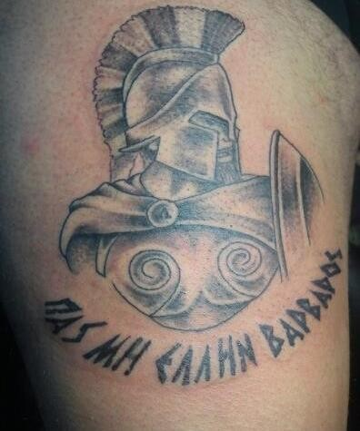 Old style pale colored Spartan&quots warrior with shield shoulder tattoo with dark black ink lettering