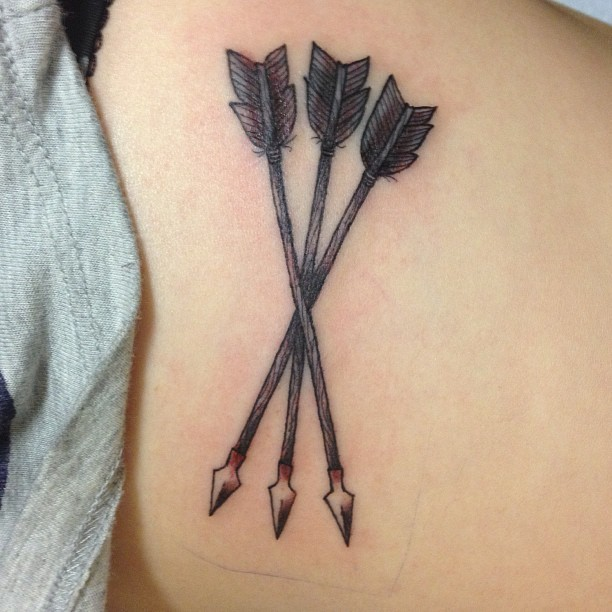 Old tribal indian arrow tattoo on girls body