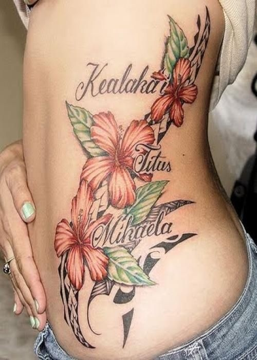 Orange hibiscus flowers with black tribal and name tattoo on ribs