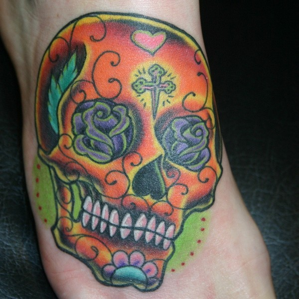 Orange sugar skull tattoo on foot