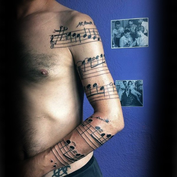 Original black ink sleeve tattoo of song notes with lettering