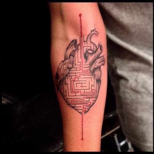 Original colored forearm tattoo of human heart with labyrinth