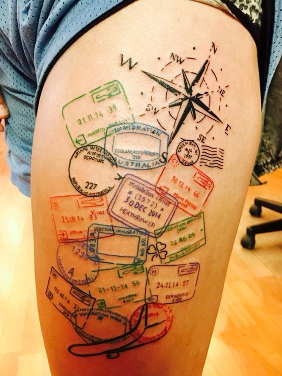 Original colorful thigh tattoo of various stamps and compass