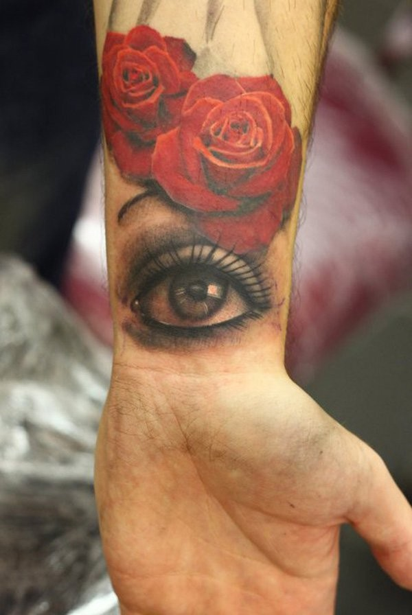 Original combined usual red colored roses with mystic eye tattoo on wrist