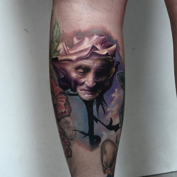Original designed and colored leg tattoo of rose stylized with old woman face