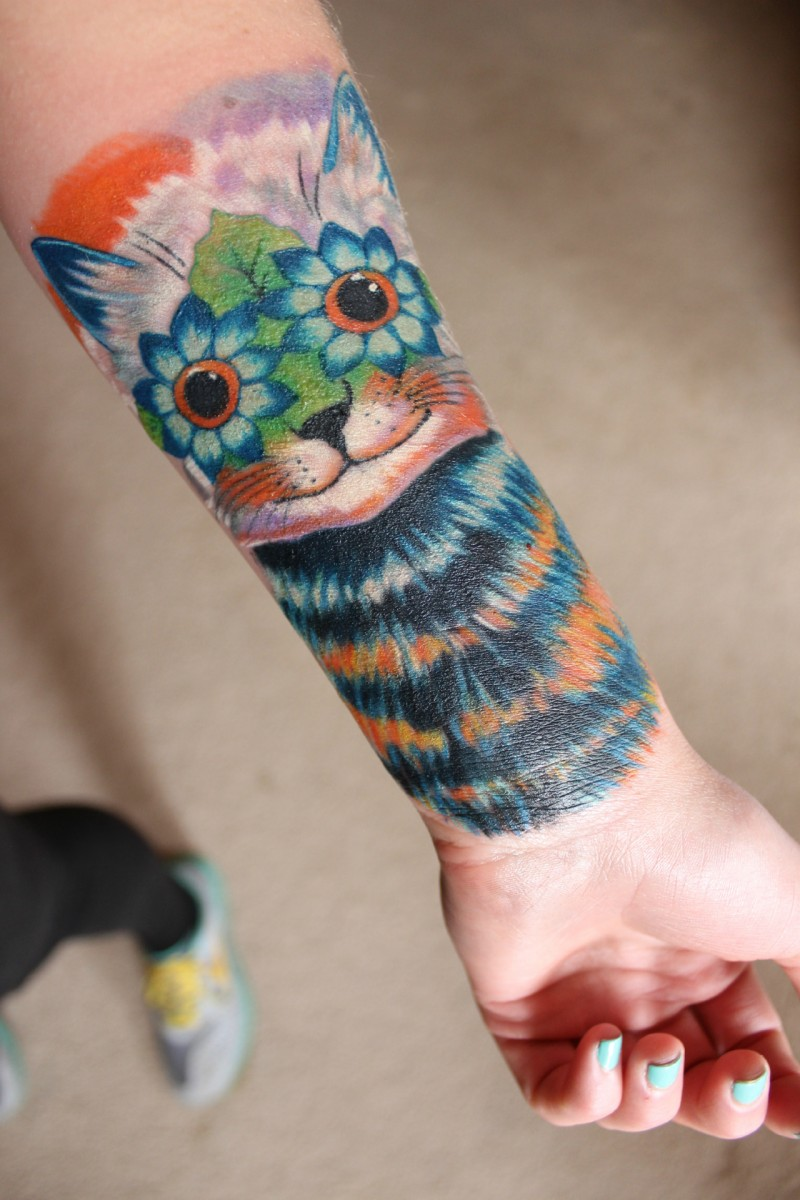 Original designed colored forearm tattoo of cat with flower eyes