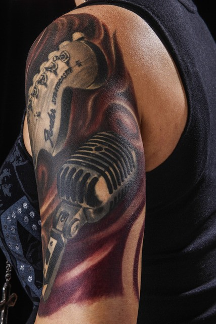 Original painted and colored shoulder tattoo of guitar with microphone