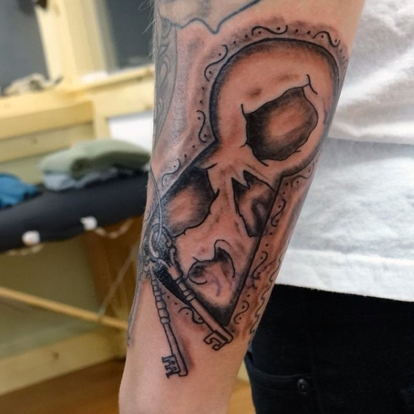 Original painted antic lock with keys and skull tattoo on arm
