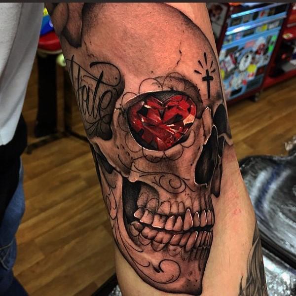 Tatuaje en el brazo, cráneo con diamante rojo en el ojo