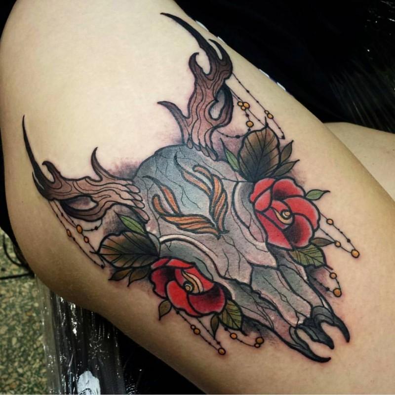 Tatuaje en el muslo,  cráneo animal multicolor con flores rojas