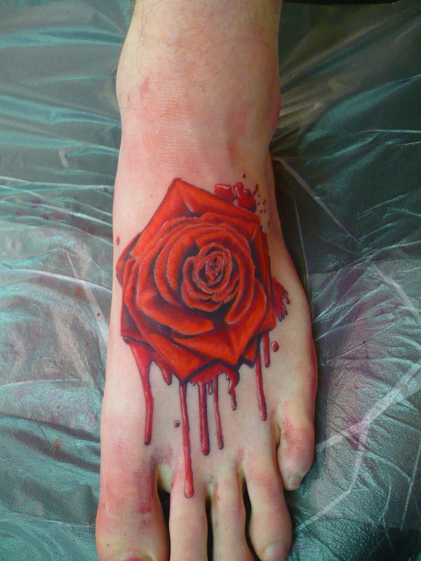 Original painted red colored bloody rose tattoo on foot