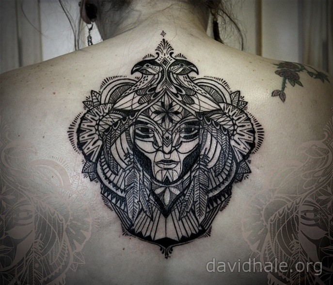 Ornamental style black ink back tattoo of mystical face