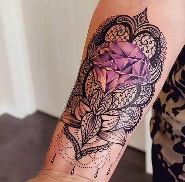 Tatuaje en el antebrazo, ornamento floral con diamante púrpura