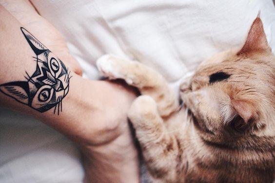 Ornamental style black ink wrist tattoo of cat head