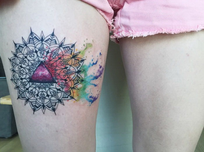 Ornamental style colored thigh tattoo of big flower with triangle