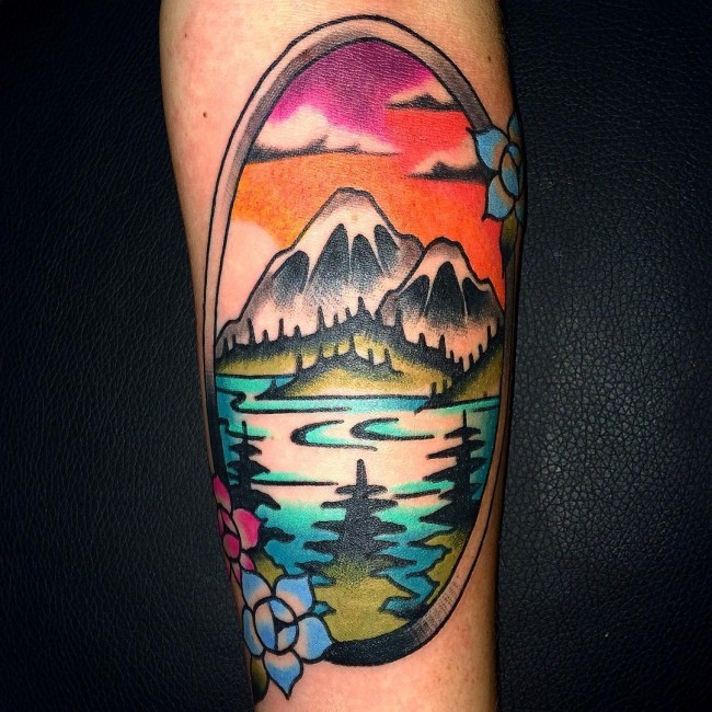 Oval shaped multicolored forearm tattoo of mountain lake with flowers
