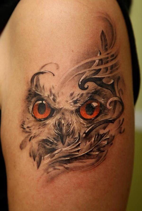 Tatuaggio colorato sul deltoide gli occhi di gufo