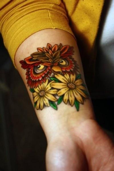 Owl with yellow flowers tattoo on wrist