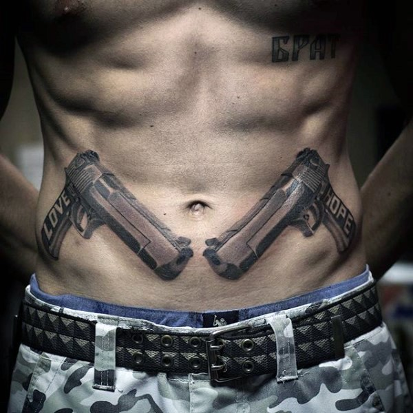 Pair of guns with lettering Love Hope gangsta style tattoo on lower belly