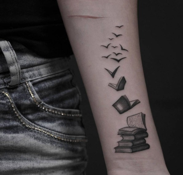 Pale of books with flock of birds forearm tattoo in small details