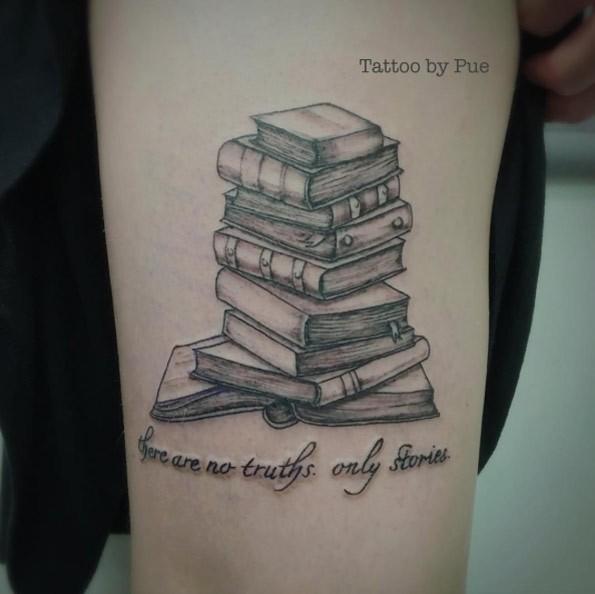 Tatuaje en el antebrazo, montón de libros diferentes y inscripción