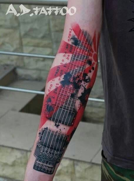 Photoshop style colored forearm tattoo of guitar with lettering