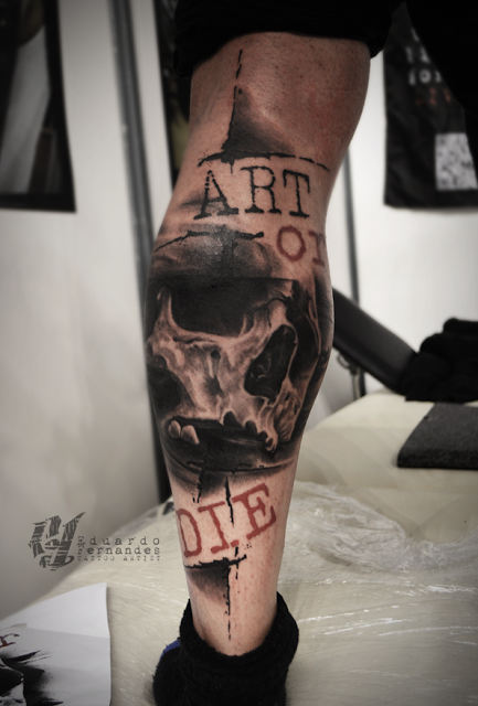 Photoshop style colored leg tattoo of human skull with lettering