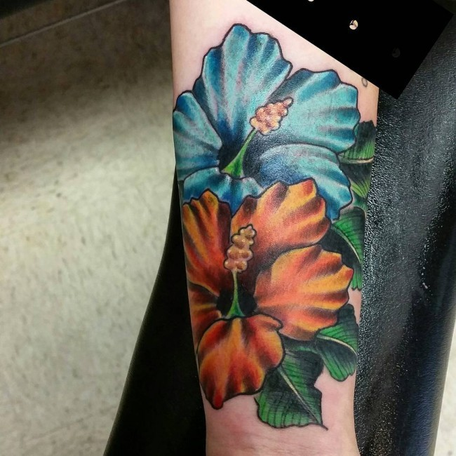 Picturesque yellow and blue hibiscus Hawaiian velvety flowers forearm tattoo