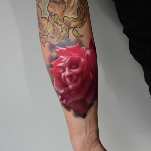 Pink colored forearm tattoo of large rose stylized with face