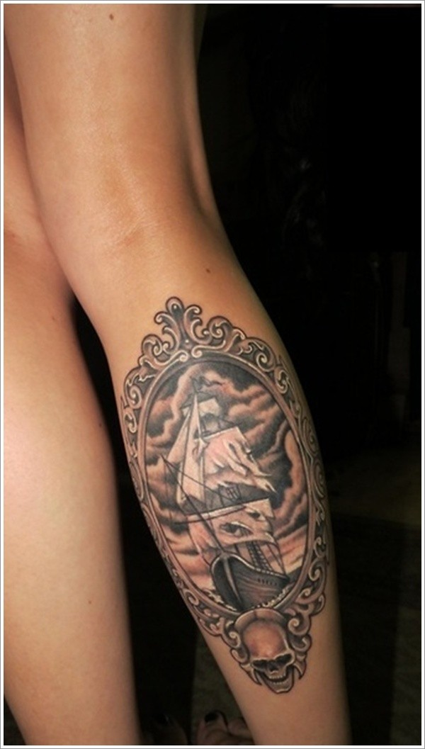 Pirate ship in frame with skull tattoo on leg